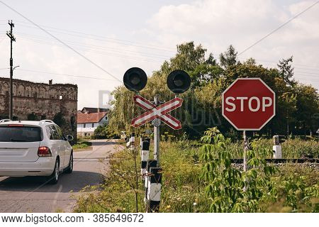 A Car Crossing Railroad With A Stop Sign. Train Rails In Country Landscape. Railroad Tracks At Sunse