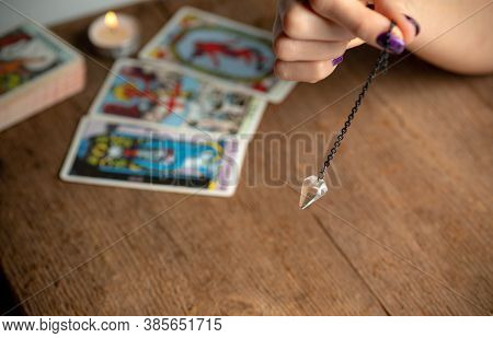 Arm Of A Dowser With Hand-held Pendulum On The Background Of A Burning Candle And Tarot Cards. Selec