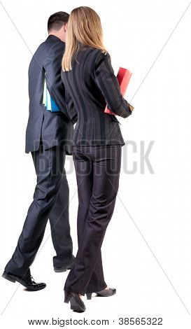 Back view of walking business team. Going young couple with books. beautiful friendly girl and guy in suit . Rear view people collection. backside view of person. Isolated over white background