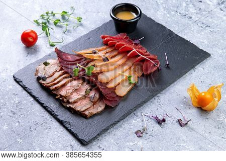 Assorted Dry-cured Meats On A Stone Background.