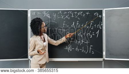 Young African American Woman Teacher In Glasses Standing At Board In Classroom And Telling Physics O