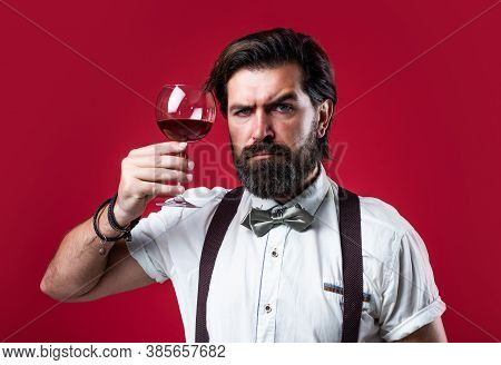 Wineglass Of Red Wine In Hand Of Male Sommelier Appreciating Drink, Barman