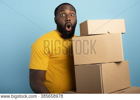 Surprised Man Holds A Lot Of Received Packages. Cyan Background