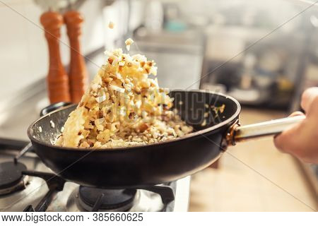 Onions And Bacon Tossed In A Pan Inside The Kitchen. Khichri Tossed In A Wok Pan