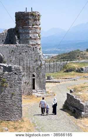 muslim family walks through the ruins of the minaret added by the Turks to the St. Stephens Church, turning it in a mosque, in the Rozafa Castle, Shkoder