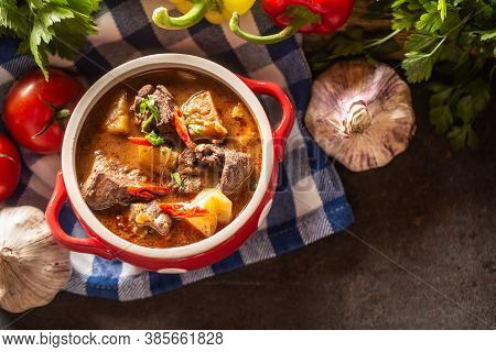Top Views Of Bowl Of Goulash Soup With Meat, Potatoes And Chillies
