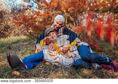 Fall Family Activities. Senior Man And Woman Relaxing In Autumn Park Lying Under Tree. People Enjoy