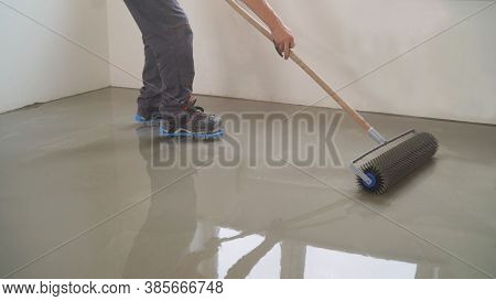 A Worker Rolls Out The Liquid Floor With A Trowel. Squeegee For Distributing The Mixture. The Worker