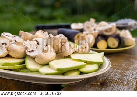 Plates With Various Fresh Vegetables And Champignon Mashrooms Prepared For Barbecue. Bell Pepper, Co