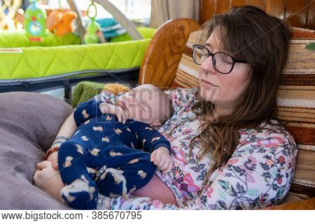 Young Woman With Glasses And Septum Ring Holds Her Young Infant Son Clothed In A Blue Romper, Both S