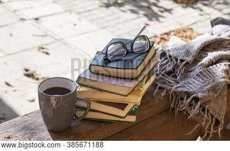 A Cup, Book And A Blanket On The Autumn Veranda In The Shade Of Trees. Cozy Place To Read And Relax