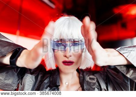 A Woman In A Futuristic Metallic Dress With Glasses Looks Ahead.