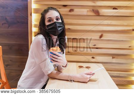 A Young Woman In A Mask From The Virus Went For Coffee. The City Is In Quarantine.