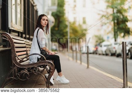 Young Beautiful Woman Waiting For The Bus At The Stop.