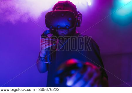 Man In A Virtual Reality Helmet. Neon Room With Vr Games.