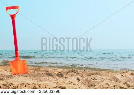 Kids Toy Orange Shovel Stuck In A Sand At The Beach Sea Shore