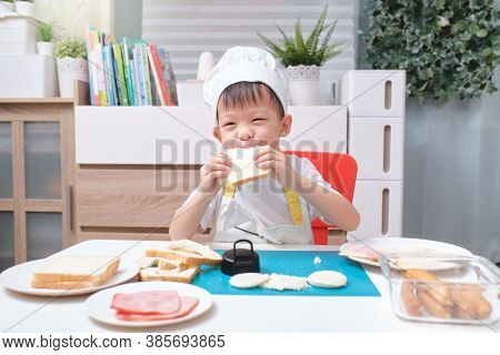 Cute Asian Boy Wearing Chef Hat And Apron Having Fun Preparing Sandwiches, Little Kid Holding And Bi