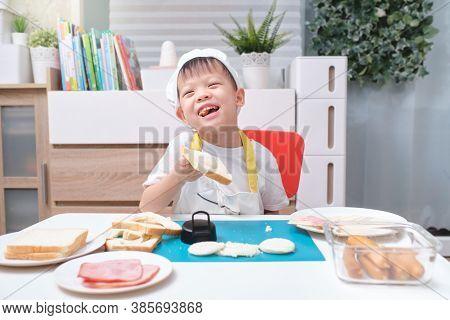 Cute Asian Boy Wearing Chef Hat And Apron Having Fun Preparing Sandwiches, Little Kid Holding Bread