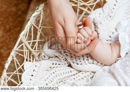 Newborn Baby Hand In Mother Hand. Happy Mother Holding Hand Of Her Newborn Children. Mom And Her Chi
