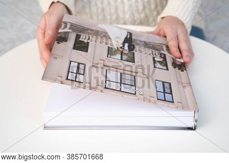 Women Hands Hold A Wedding Photo Book On The Table. Convenient, Beautiful And Long-lasting Storage O