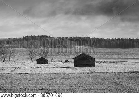 Two Old Barn Houses Stand On The Autumn Fields By A Lake In The Northern Finland. The Skies Are Quit