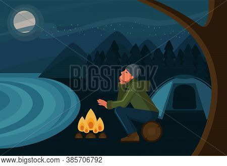The Man Warms His Hands And The Fire And Looks At The Starry Sky. Tourist In A Campsite. Outdoor Rec