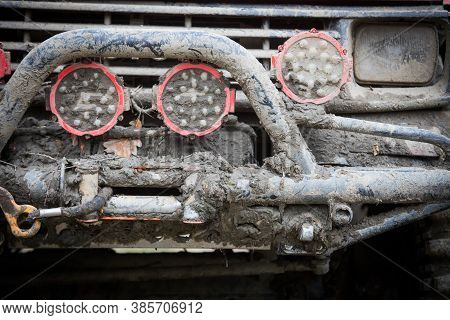 Close Up Shot Of An Off Road Car Front, Covered In Mud, With Bullbar And Headlights.