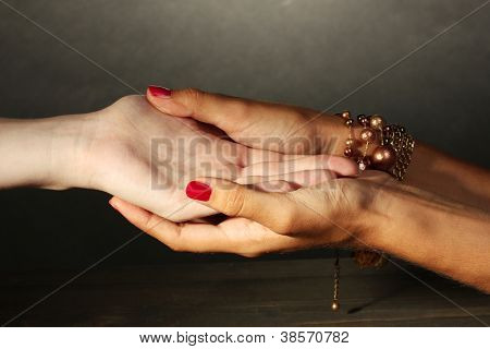 reading the lines hand in a woman's hands on grey backcground