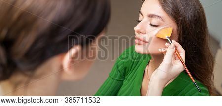 Make Up Artist Applying Professional Make Up Of Tonal Foundation On The Face Of Beautiful Young Cauc