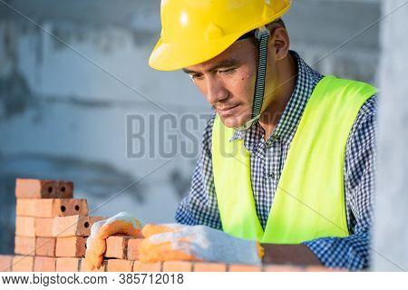 Industrial Bricklayer Installing Bricks On Construction Site,bricklayer Worker Installing Brick Maso