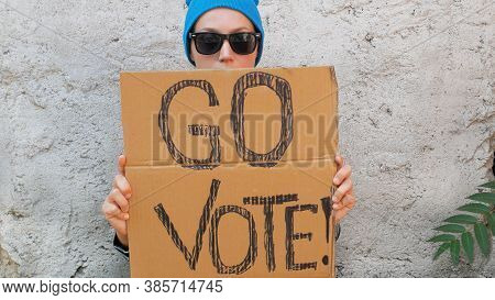 Woman Shows Cardboard With Go Vote Sign On Brick Wall Urban Background. Voting Concept. Make The Pol