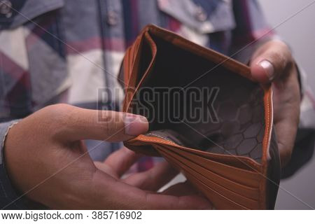 Man Showing Empty Wallet. Poverty Finance Business Bankruptcy And Debt Concept.