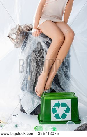 Partial View Of Young Woman In Silk Dress Sitting On Stool Wrapped In Plastic Bag Near Trash Bin Wit