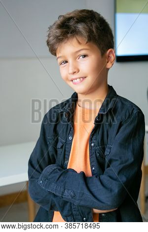 Portrait Of Caucasian Schoolboy With Folded Hands. Lovely Handsome Kid In Jeans Shirt Posing In Clas