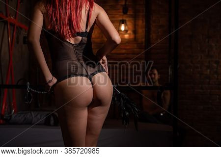 A Redhead Woman With A Beautiful Booty In Black Underwear Stands With A Whip And Dominates The Man D