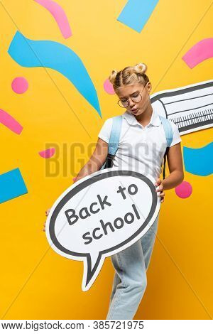 Discouraged Schoolgirl Holding Speech Bubble With Back To School Lettering Near Colorful Paper Eleme
