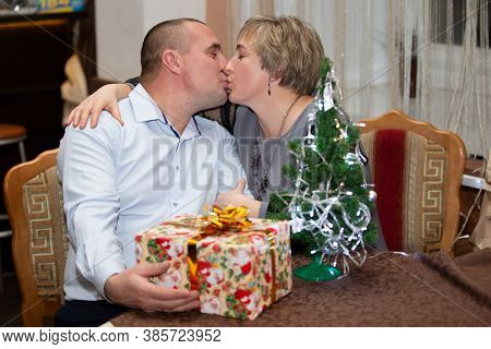 Middle-aged Couple On Christmas Evening. Ordinary Man And Woman Kiss On Christmas Background