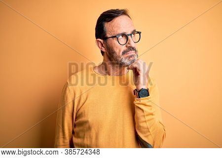 Middle age hoary man wearing casual sweater and glasses over isolated yellow background with hand on chin thinking about question, pensive expression. Smiling with thoughtful face. Doubt concept.