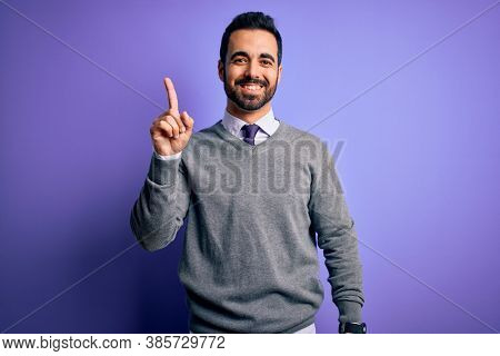 Handsome businessman with beard wearing casual tie standing over purple background showing and pointing up with finger number one while smiling confident and happy.