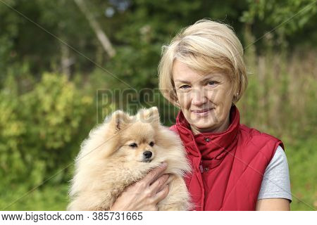Happy Senior Woman Is Holding Her Pomeranian Spitz Dog On Hands, Hugging Puppy Outdoors And Smiling.