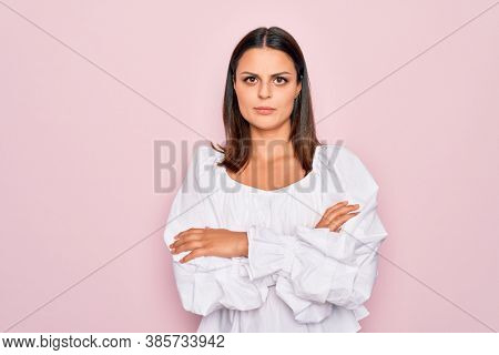 Young beautiful brunette woman wearing casual white dress standing over pink background skeptic and nervous, disapproving expression on face with crossed arms. Negative person.