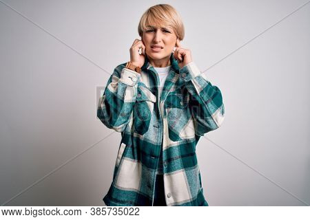 Young blonde woman with short hair wearing casual retro green shirt over isolated background covering ears with fingers with annoyed expression for the noise of loud music. Deaf concept.