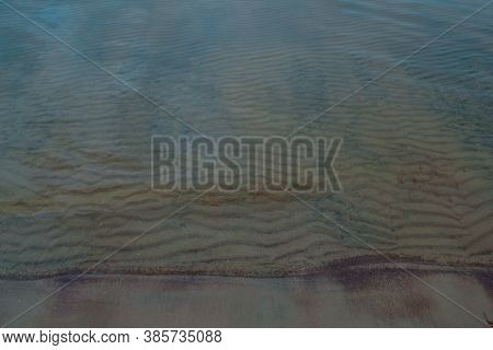 Colored Sandy Shore Of The Sea Lake With Waves At The Bottom And Ripples, Blue Yellow-green Coast
