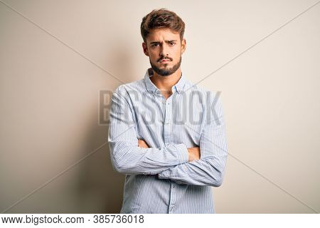 Young handsome man with beard wearing striped shirt standing over white background skeptic and nervous, disapproving expression on face with crossed arms. Negative person.