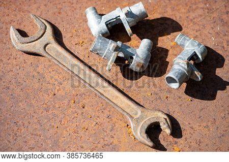 Old Spanner On Aold Wrench And Metal Parts On A Rusty Sheet Of Metal, Close-up, Selective Focus. Rus