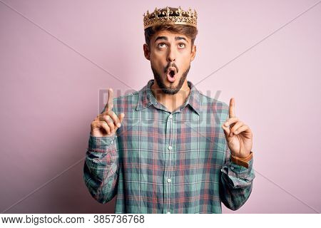 Young man with beard wearing golden crown of king standing over isolated pink background amazed and surprised looking up and pointing with fingers and raised arms.