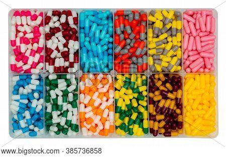 Top View Of Colorful Capsule Pills In  Plastic Box. Antibiotic Drugs, Painkiller Medicine, Vitamins,