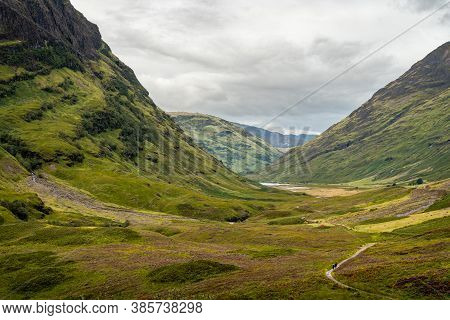 Scenic View Of Glen Coe, Scottish Highlands, Uk. Tranquil Scene Of Ravine, Stream And Hiking Path In