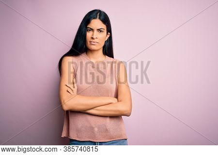 Young beautiful hispanic fashion woman wearing casual sweater over pink background skeptic and nervous, disapproving expression on face with crossed arms. Negative person.