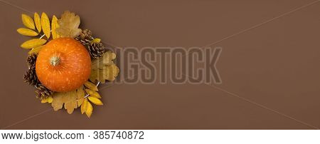 Orange Pumpkin, Dried Leaves And Fir Cones On Plate Flat Lay On Brown Background. Autumn Harvest. Ha